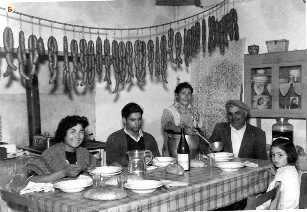 famiglia sarda in cucina, con salsicce appese ad asciugare